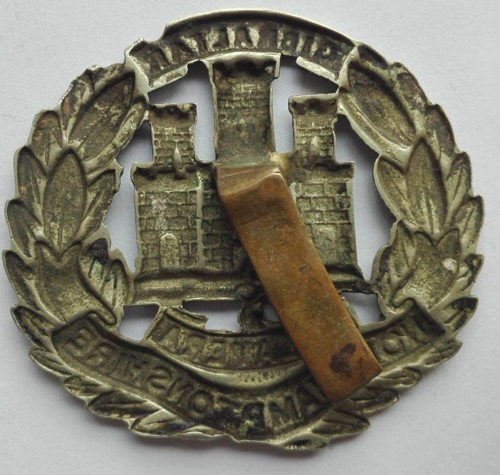 Reverse of british cap badge showing the slider for attachment to the beret.