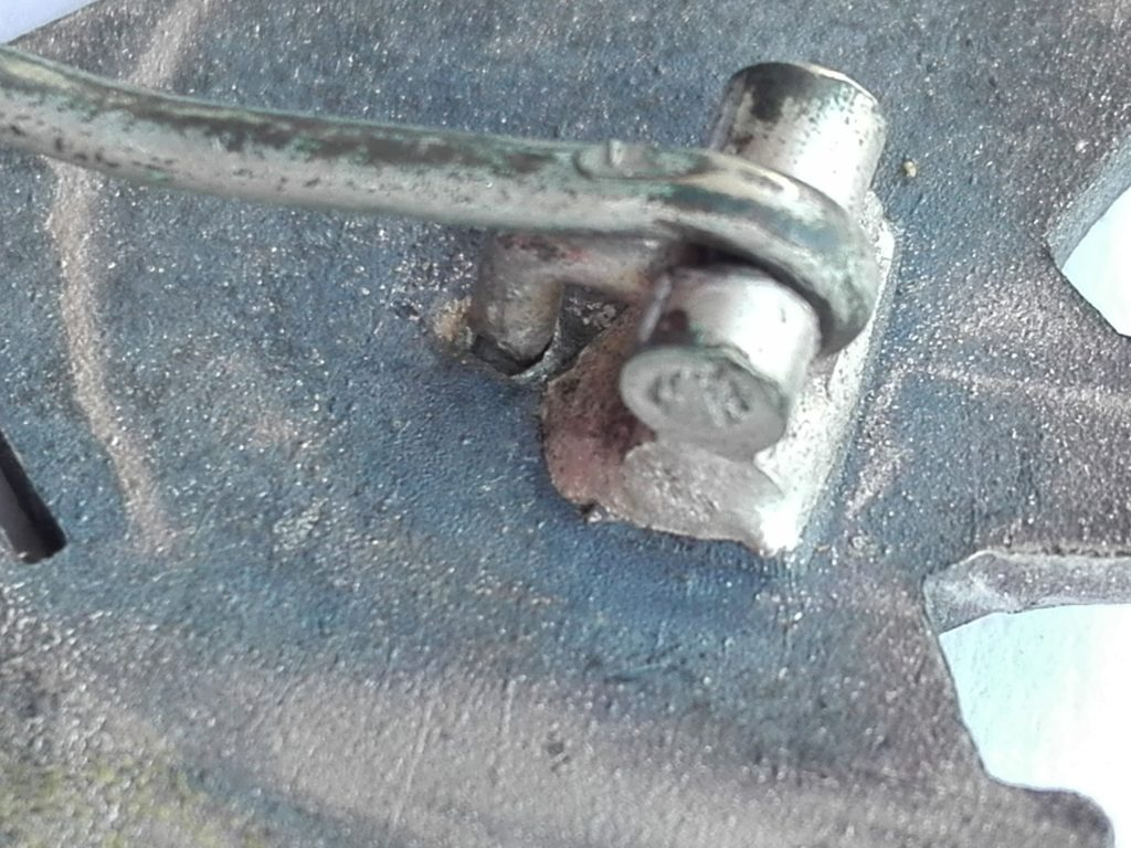 A solid hinge block affixed to the reverse of the IAB eagle. Round wire Pin
