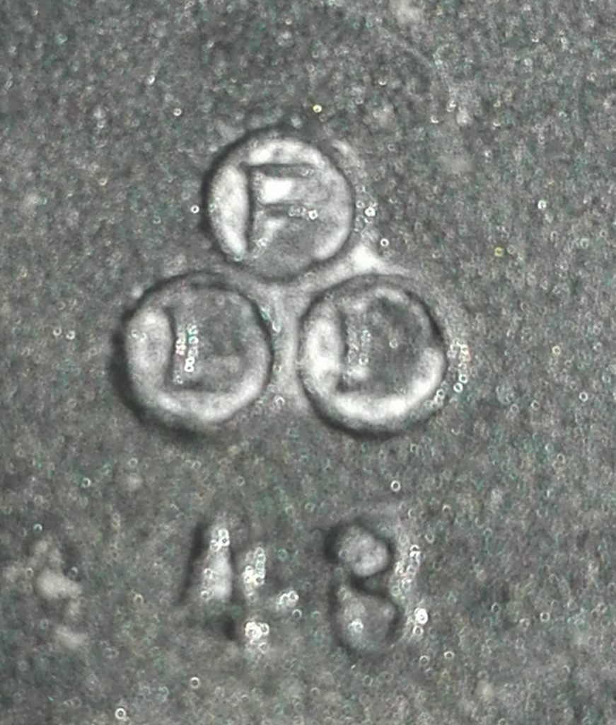 Maker mark for FLL (within three circles) in raised letters above the number 43