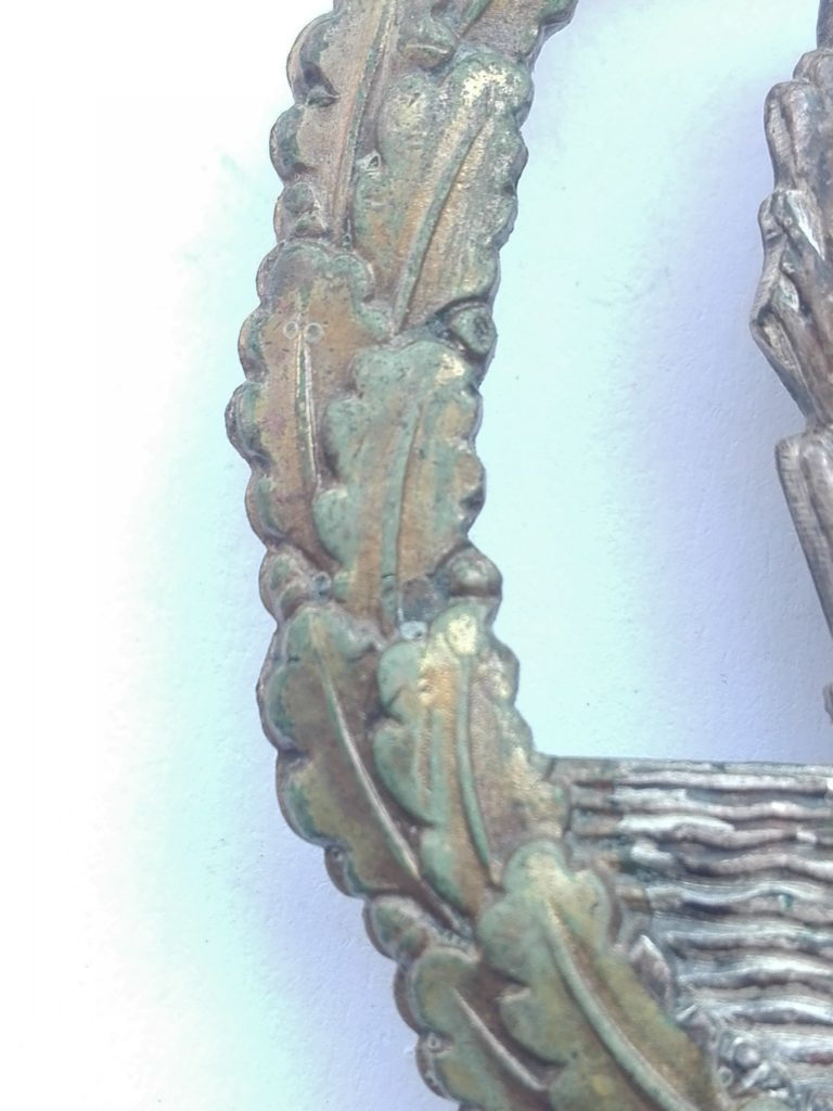 Although difficult to determine, due to the lighting, the early stages of verdigris (green patina) can be seen in the guilded areas of the oakleaf wreath.